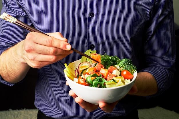 Un homme en chemise tient un poke bol avec du saumon, du brocoli, du riz, du fromage aux carottes et du chuha