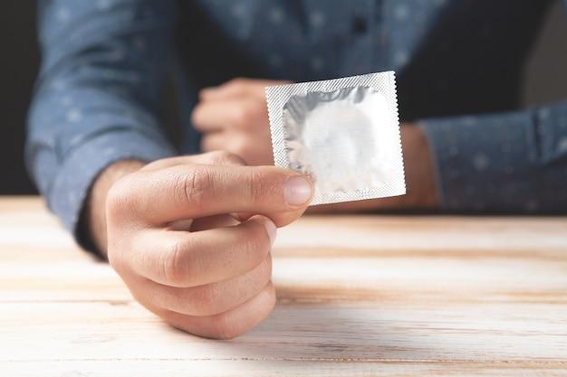 Un homme en chemise tient un préservatif