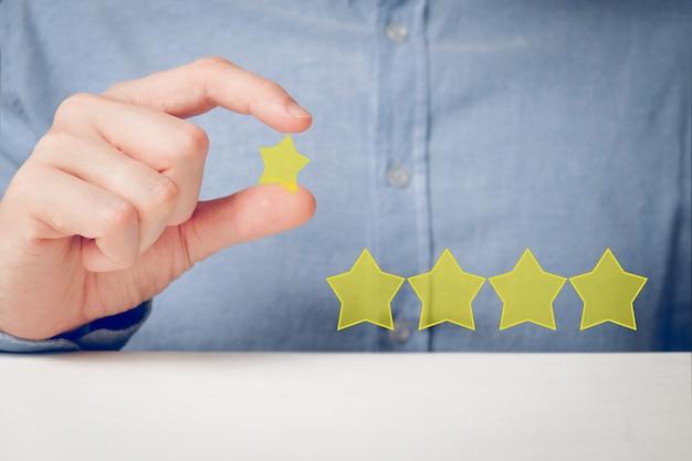 Un homme en chemise veut abstraitement mettre une cote de cinq étoiles sur ses mains. meilleur score