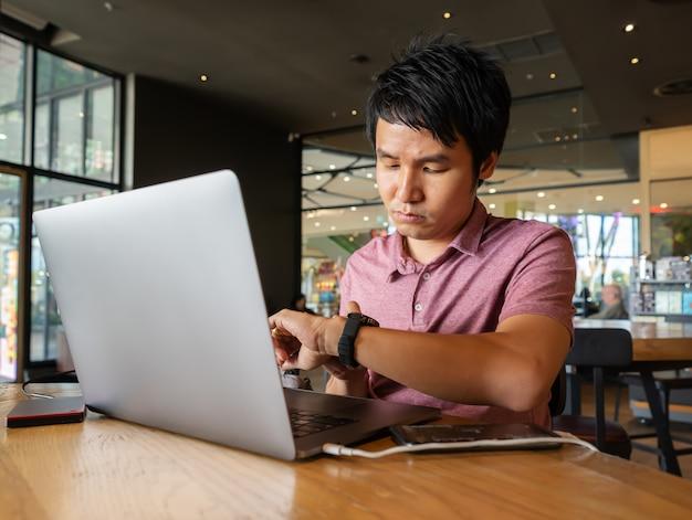 Homme cherche sa montre intelligente avec ordinateur portable au café