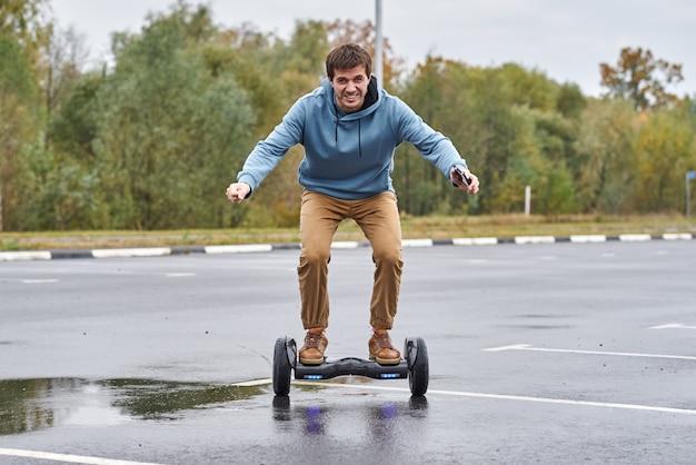 Homme à cheval sur le hoverboard et utilisant un smartphone en plein air