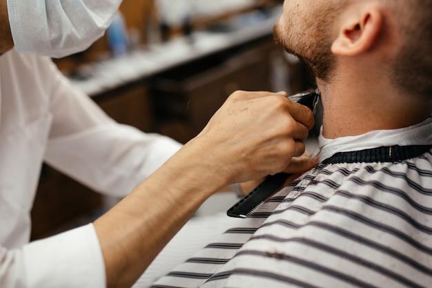 Un homme a les cheveux coupés sur sa barbe dans un salon de coiffure