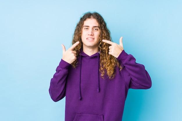 Homme cheveux longs posant des sourires isolés, pointant du doigt la bouche.