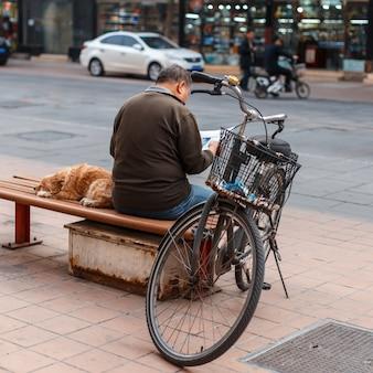 Homme avec un chien assis sur un banc et lisant un journal