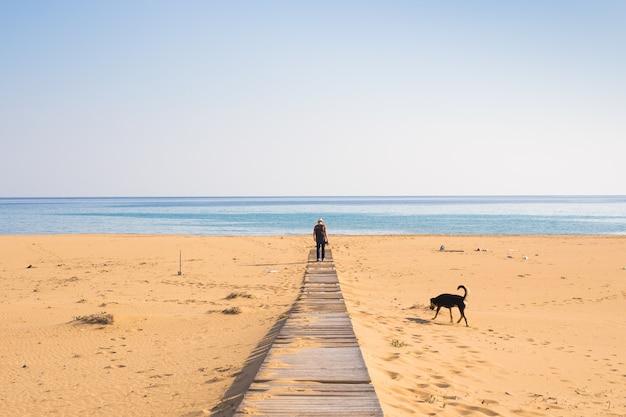 Homme avec chien marchant sur le chemin en bois sur la plage et regardant au loin l'océan.
