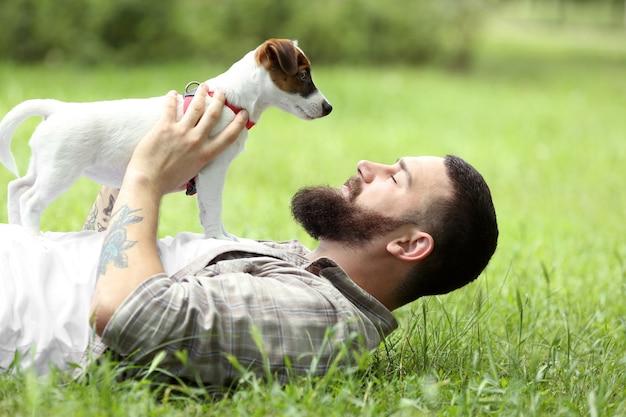 Homme avec chien mignon dans le parc du printemps