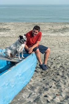 Homme avec un chien noir et blanc à la plage
