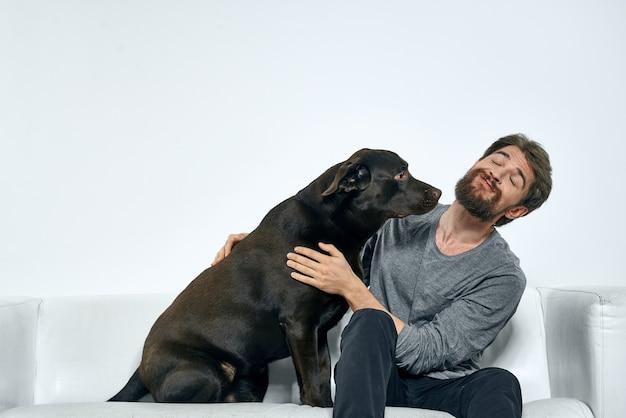 Homme avec un chien noir sur le canapé