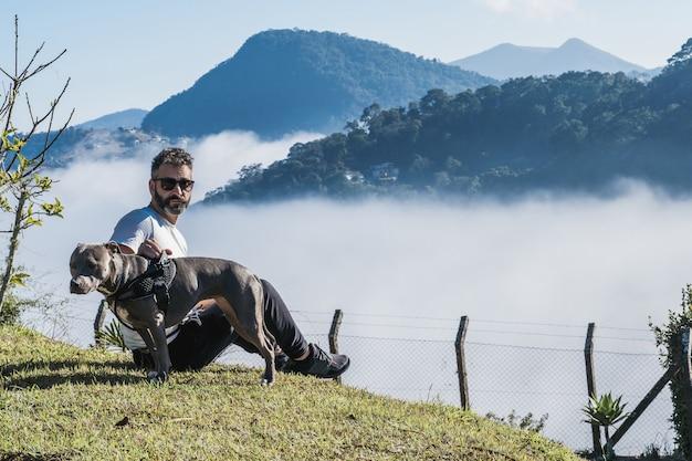 Un homme et un chien pit bull admirant la nature et le grand brouillard dans les montagnes de petrã³polis, au brésil, couvrant la ville sous les nuages. relation affectueuse entre l'homme et l'animal.