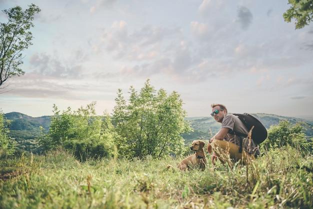 Homme avec un chien se reposant sur le pré