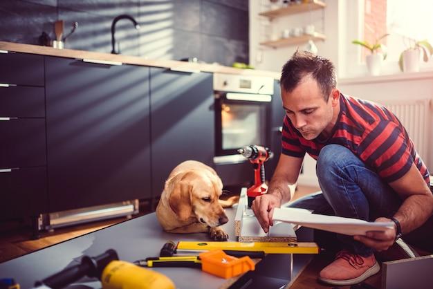 Homme avec chien vérifiant les plans lors de la construction d'armoires de cuisine