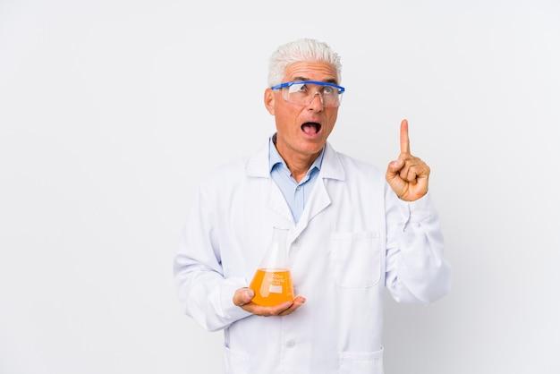 Homme chimique mature isolé pointant à l'envers avec la bouche ouverte.
