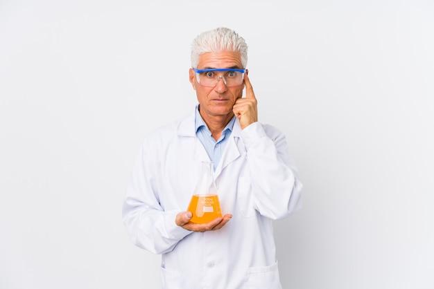 Homme chimique mature isolé pointant le temple avec le doigt, pensant, concentré sur une tâche.