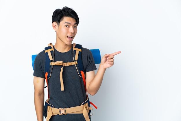 Homme chinois alpiniste avec sur blanc doigt pointé sur le côté et présentant un produit
