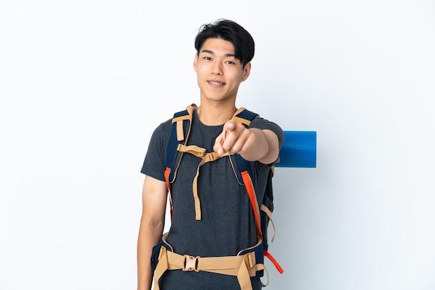 Homme chinois alpiniste avec isolé sur un espace blanc pointant vers l'avant avec une expression heureuse