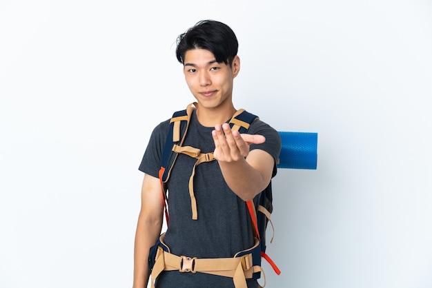 Homme chinois alpiniste avec isolé sur fond blanc invitant à venir avec la main. heureux que tu sois venu