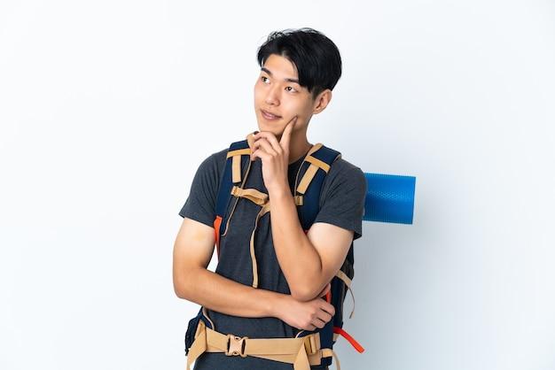 Homme chinois alpiniste avec isolé sur fond blanc en pensant à une idée tout en regardant
