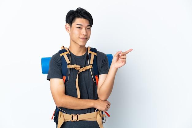 Homme chinois alpiniste avec isolé sur mur blanc doigt pointé sur le côté