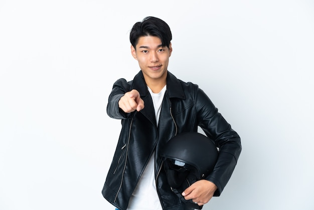 Homme chinois avec un casque de moto isolé sur un mur blanc pointant vers l'avant avec une expression heureuse