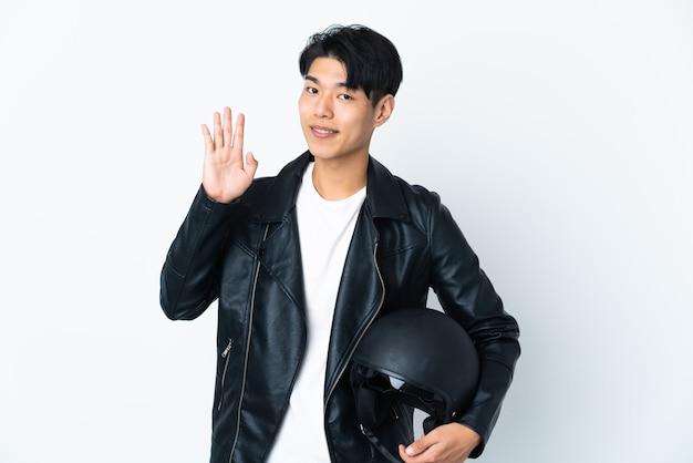Homme chinois avec un casque de moto isolé sur un mur blanc saluant avec la main avec une expression heureuse