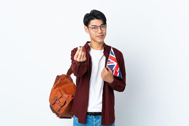 Homme chinois tenant un drapeau britannique isolé sur fond violet faisant le geste de l'argent