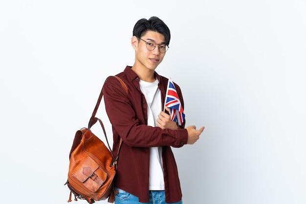 Homme chinois tenant un drapeau britannique isolé sur mur violet pointant vers l'arrière