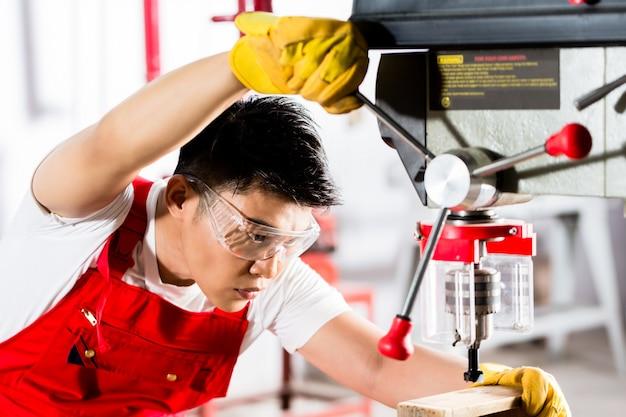 Homme chinois travaillant avec perceuse en usine