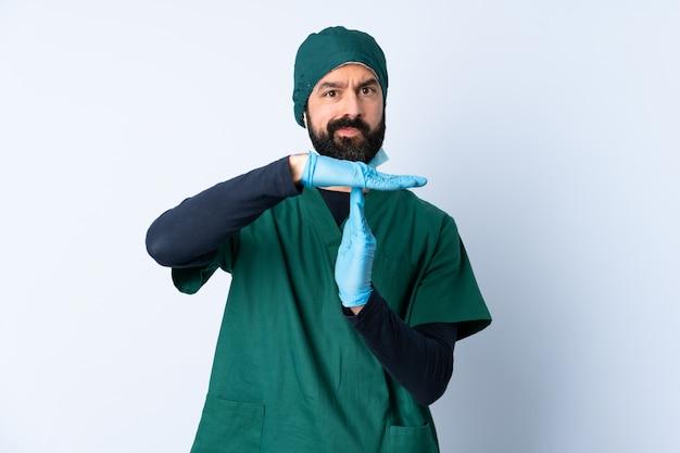 Homme chirurgien en uniforme vert sur un mur isolé faisant un geste de temporisation