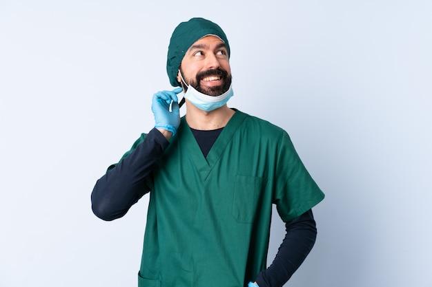 Homme chirurgien en uniforme vert sur un mur isolé en pensant à une idée