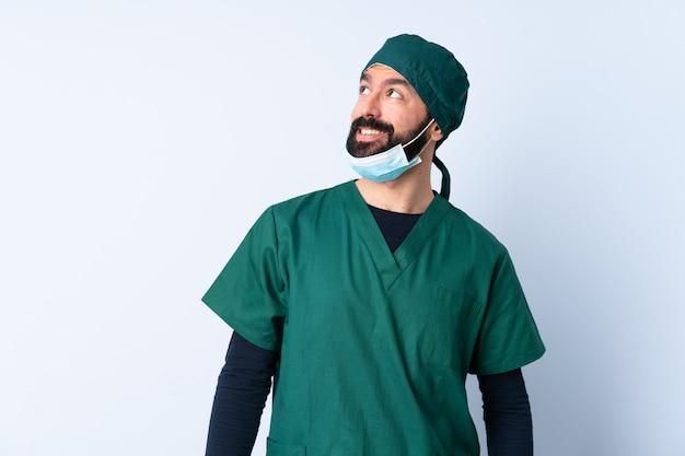 Homme chirurgien en uniforme vert sur mur penser une idée tout en levant