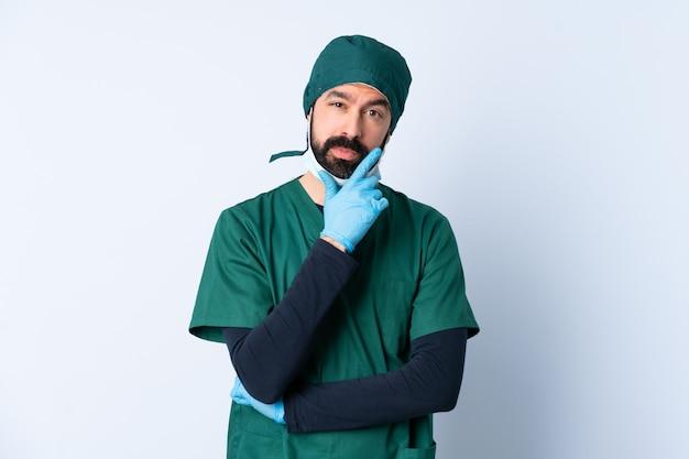 Homme chirurgien en uniforme vert sur la pensée du mur