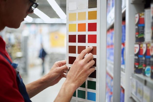 Homme choisissant un échantillon approprié de la peinture désirée