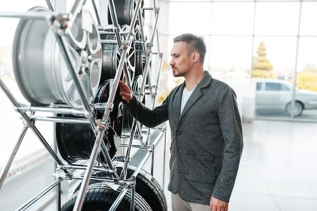 Homme choisissant des roues pour une nouvelle voiture dans la salle d'exposition.