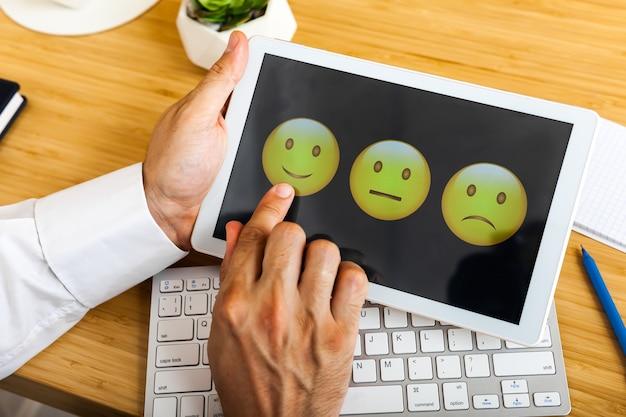 Homme choisissant son opinion avec des visages souriants sur l'écran tactile