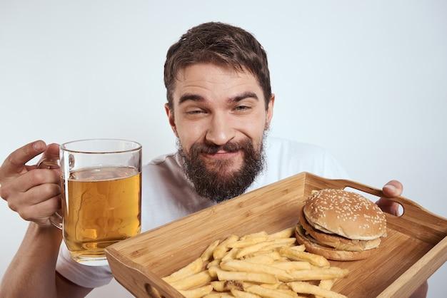 Homme avec chope de bière et nourriture sur plateau en bois