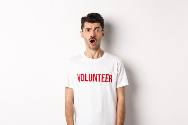 Homme choqué et confus en t-shirt bénévole regardant la caméra sans voix, debout sur fond blanc.