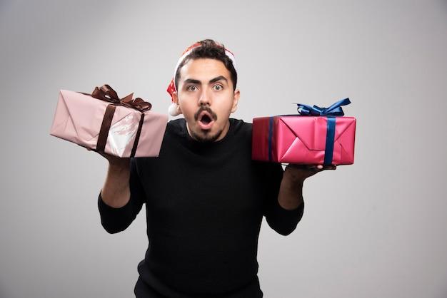 Un homme choqué dans un chapeau de père noël tenant des cadeaux du nouvel an.