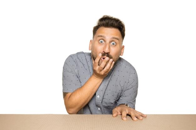 Homme choqué et étonné ouvrant le plus gros colis postal
