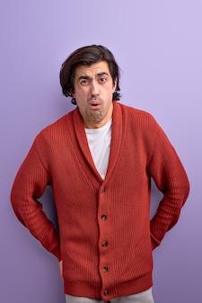 Un homme choqué réagit à quelque chose d'incroyable isolé sur un mur violet