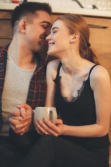 Homme chuchotant quelque chose à sa femme tout en ayant une pause-café dans la cuisine sur le sol