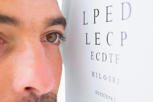 Homme ciblé sur les lettres de test oculaire