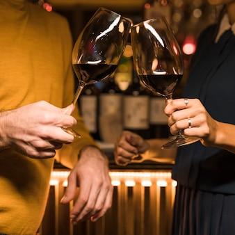 Homme claquant des verres de boisson avec femme