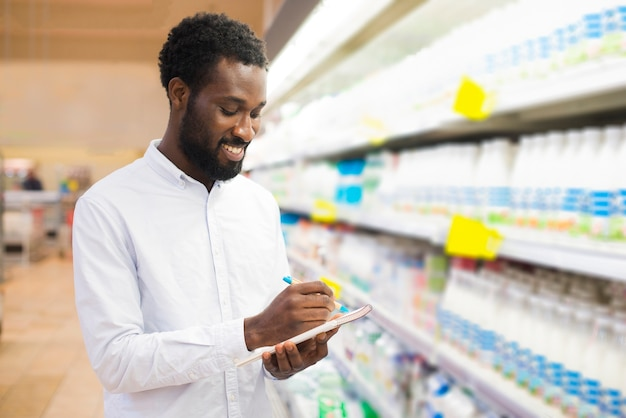 Un homme coche des articles dans sa liste d'épicerie