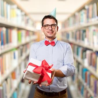 L'homme coiffé d'un chapeau rouge noeud papillon et partie. tenir cadeau.
