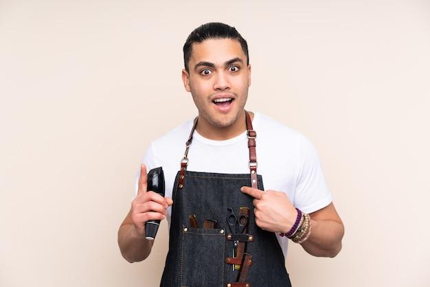 Homme de coiffeur dans un tablier isolé sur fond beige avec une expression faciale surprise