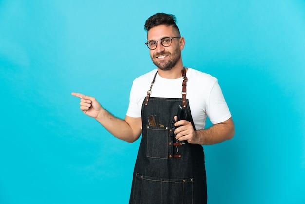 Homme de coiffeur dans un tablier pointant le doigt sur le côté