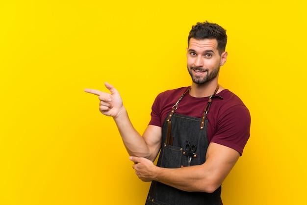 Homme coiffeur dans un tablier, pointant le doigt sur le côté