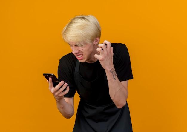 Homme de coiffeur professionnel en colère en tablier en regardant l'écran de son smartphone se déchaînant debout sur un mur orange
