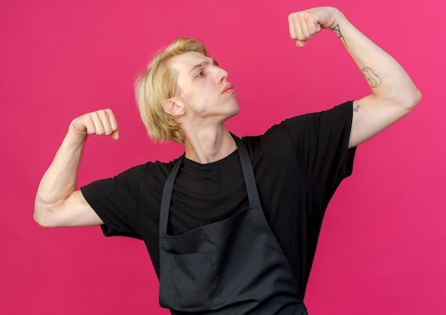 Homme de coiffeur professionnel en tablier levant les poings posant à la caméra comme athlète