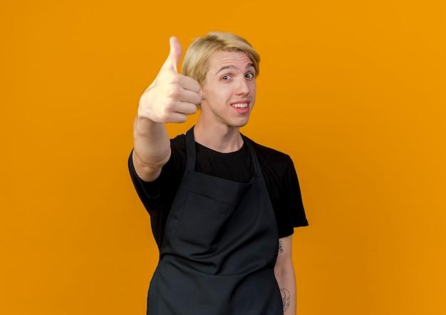 Homme de coiffeur professionnel en tablier regardant à l'avant souriant montrant les pouces vers le haut debout sur le mur orange